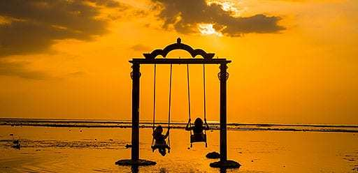 PMGY volunteer in Bali swinging at sunset on Gili T during their volunteer weekend trips in Bali